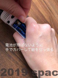 電池が飛ばないように気をつけて紐を引っ張る
